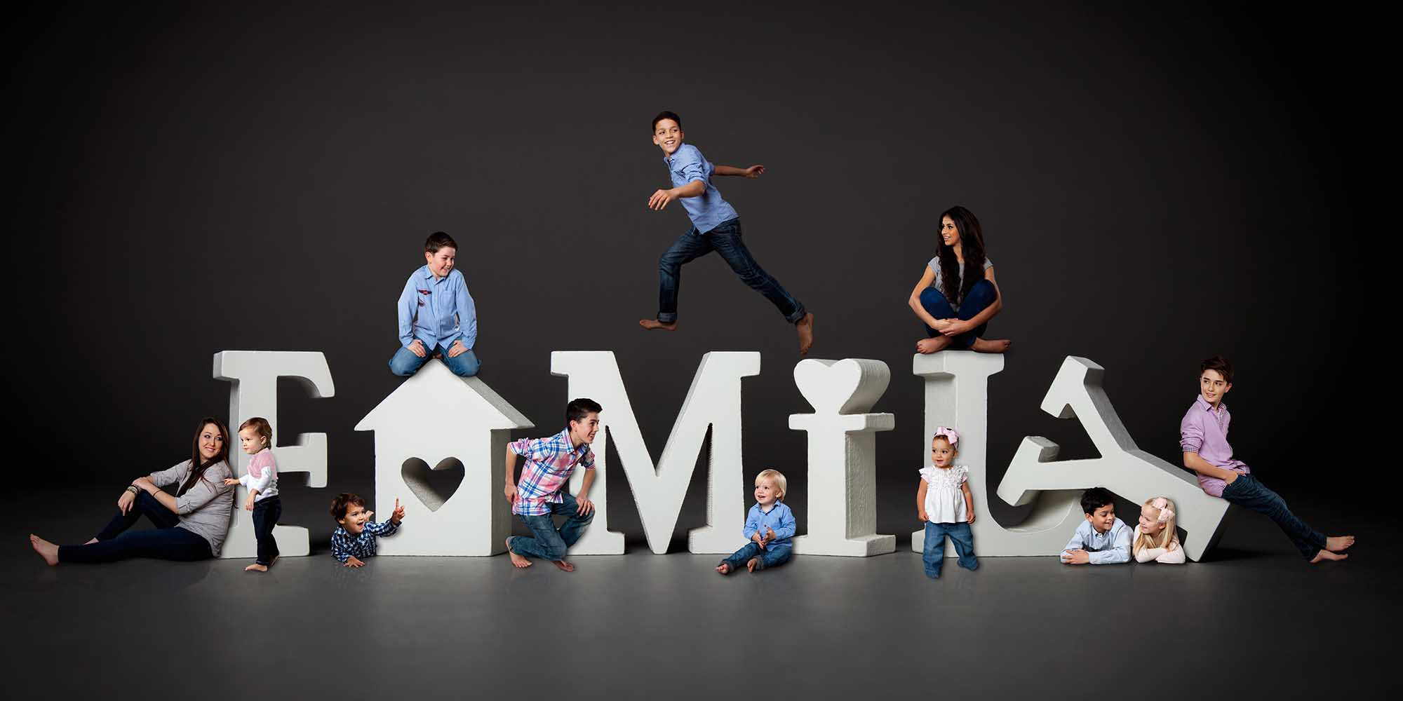 Creative Family Portrait with Children jumping and gathering around large letters that spell family.